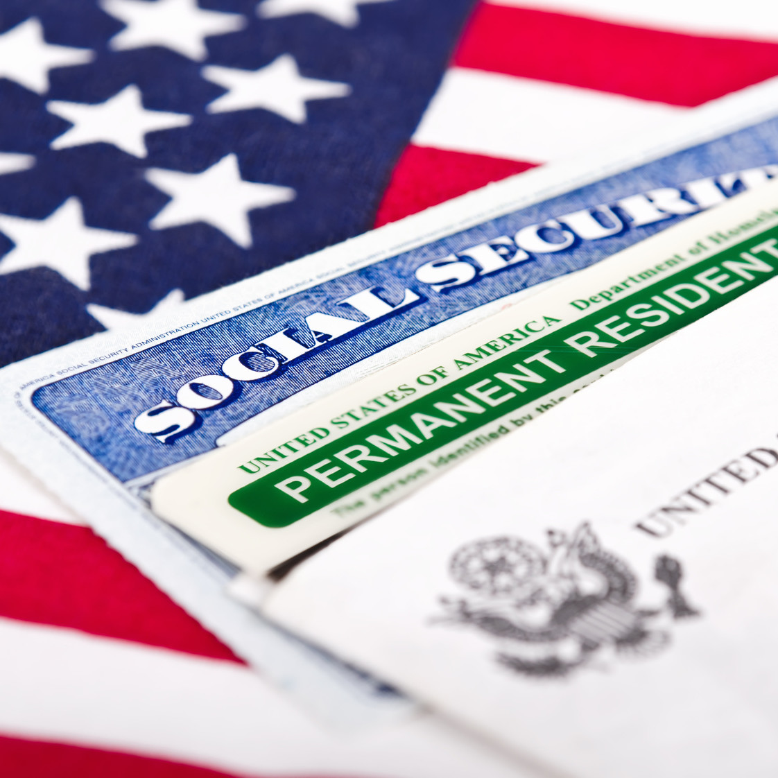 United States of America social security and green card with US flag on the background. Immigration concept. Closeup with shallow depth of field.